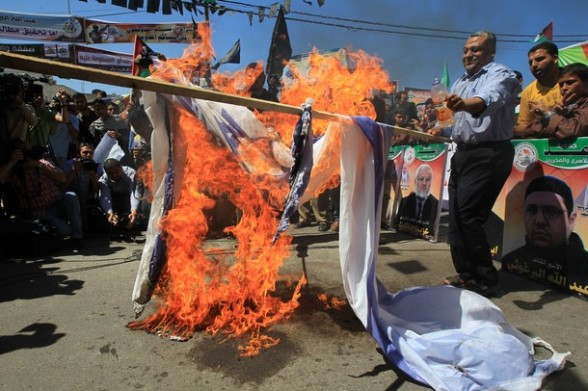 Palestinian protesters burn an Israeli flag during rally in solidarity with Palestinian prisoners held in Israel in Gaza City on April 17, 2012.  Some 1,200 Palestinian prisoners held in Israeli jails have begun a hunger strike and another 2,300 are refusing food for one day, according to a spokeswoman for the Israel Prisons Service (IPS) as Palestinians across the West Bank and Gaza Strip were marking Prisoners' Day in solidarity with the 4,700 Palestinian inmates of Israeli jails. AFP PHOTO/MAHMUD HAMS
