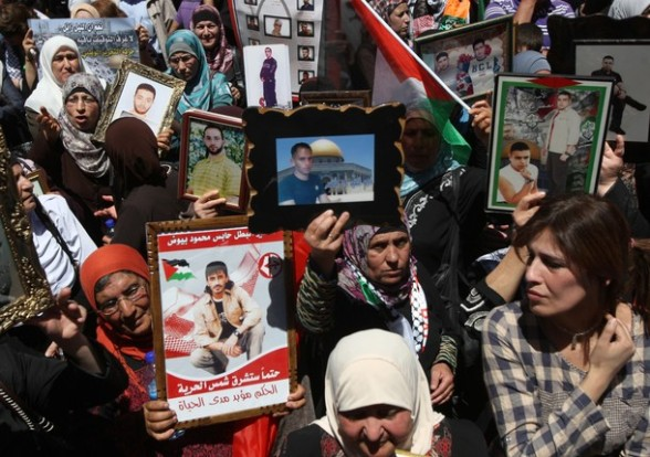 Palestinian women hold portraits of their loved ones, who are jailed in Israeli prisons, during a demonstration to mark the Prisoners' Day outside Israel?s Ofer prison, between Jerusalem and Ramallah on April 17, 2012. At least 1,200 Palestinian inmates of Israeli jails began an open-ended hunger strike as rallies across the occupied territories marked Prisoners' Day. AFP PHOTO/ABBAS MOMANI