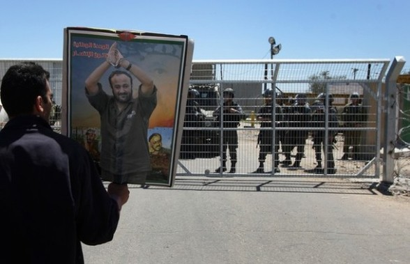 A Palestinian protester holds a picture of jailed Fatah leader Marwan Barghuti during a demonstration to mark the Prisoners' Day outside Israel?s Ofer prison, between Jerusalem and Ramallah on April 17, 2012. At least 1,200 Palestinian inmates of Israeli jails began an open-ended hunger strike as rallies across the occupied territories marked Prisoners' Day. AFP PHOTO/ABBAS MOMANI