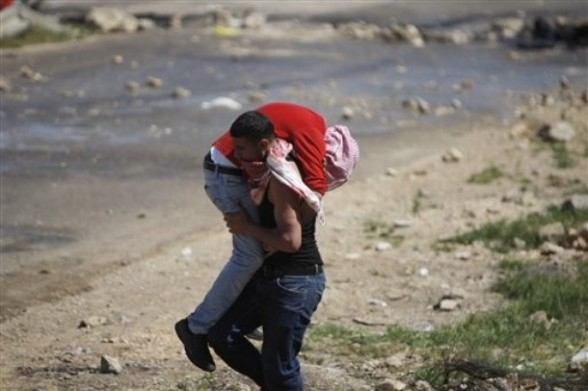 """A Palestinian carries an injured demonstrator during clashes with Israeli troops outside Ofer military prison near the West Bank city of Ramallah, on the annual """"Prisoners' Day"""", Tuesday, April 17, 2012.  Hundreds of Palestinian prisoners held by Israel launched a hunger strike on Tuesday, officials said, protesting their conditions and demanding an end to detentions without trial as the Palestinians marked their annual day of solidarity with the inmates.(AP Photo/Majdi Mohammed)"""
