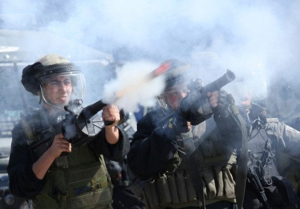 Israeli soldiers fire teargas during clashes with Palestinian protesters following a demonstration to mark the Prisoners' Day near Israel?s Ofer prison, between Jerusalem and Ramallah on April 17, 2012. At least 1,200 Palestinian inmates of Israeli jails began an open-ended hunger strike as rallies across the occupied territories marked Prisoners' Day. AFP PHOTO/ABBAS MOMANI
