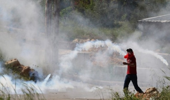 A Palestinian protester walks amid teargas fired by Israeli soldiers during a demonstration to mark the Prisoners' Day near Israel?s Ofer prison, between Jerusalem and Ramallah on April 17, 2012. At least 1,200 Palestinian inmates of Israeli jails began an open-ended hunger strike as rallies across the occupied territories marked Prisoners' Day. AFP PHOTO/ABBAS MOMANI