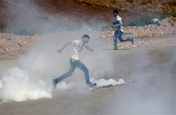 """Palestinian demonstrator kicks a tear gas canister towards Israeli troops during clashes outside Ofer military prison near the West Bank city of Ramallah, on the annual """"Prisoners' Day"""", Tuseday, April 17, 2012. Hundreds of Palestinian prisoners held by Israel launched a hunger strike on Tuesday, officials said, protesting their conditions and demanding an end to detentions without trial as the Palestinians marked their annual day of solidarity with the inmates.(AP Photo/Majdi Mohammed)"""