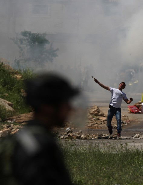 A Palestinian protester throws a stone towards the Israeli soldiers during clashes following a demonstration to mark the Prisoners' Day near Israel?s Ofer prison, between Jerusalem and Ramallah on April 17, 2012. At least 1,200 Palestinian inmates of Israeli jails began an open-ended hunger strike as rallies across the occupied territories marked Prisoners' Day. AFP PHOTO/ABBAS MOMANI