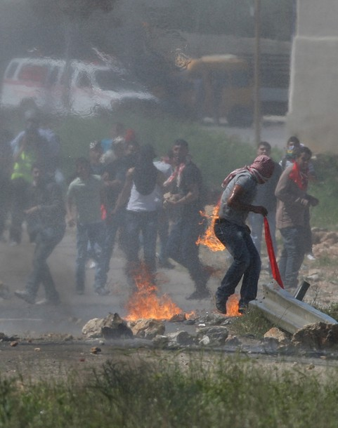 A Palestinian protester accidentally sets himself on fire while throwing a Molotov cocktail towards the Israeli soldiers during clashes following a demonstration to mark the Prisoners' Day near Israel?s Ofer prison, between Jerusalem and Ramallah on April 17, 2012. At least 1,200 Palestinian inmates of Israeli jails began an open-ended hunger strike as rallies across the occupied territories marked Prisoners' Day. AFP PHOTO/ABBAS MOMANI