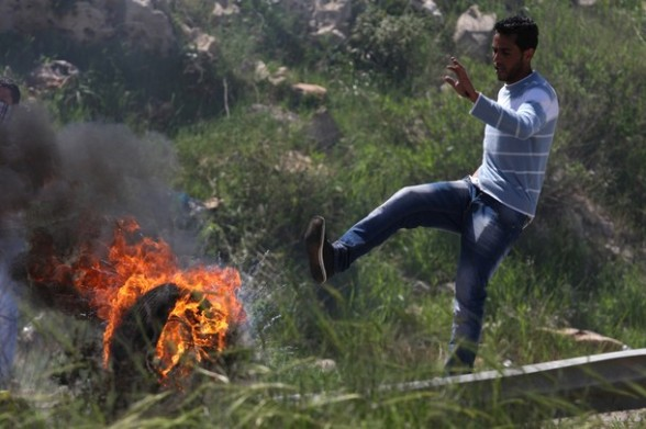 A Palestinian protester rolls a burning tire during clashes with Israeli soldiers following a demonstration to mark the Prisoners' Day near Israel?s Ofer prison, between Jerusalem and Ramallah on April 17, 2012. At least 1,200 Palestinian inmates of Israeli jails began an open-ended hunger strike as rallies across the occupied territories marked Prisoners' Day. AFP PHOTO/ABBAS MOMANI
