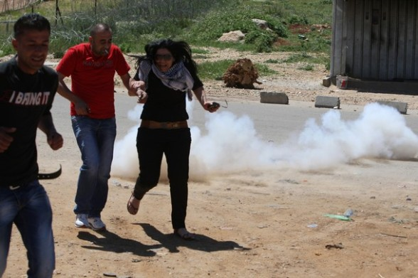 Palestinian protesters run for cover from a teargas fired by Israeli soldiers during a demonstration to mark the Prisoners' Day near Israel?s Ofer prison, between Jerusalem and Ramallah on April 17, 2012. At least 1,200 Palestinian inmates of Israeli jails began an open-ended hunger strike as rallies across the occupied territories marked Prisoners' Day. AFP PHOTO/ABBAS MOMANI