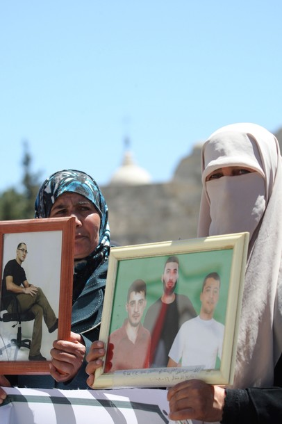 Two Muslim Palestinian women hold up pictures of jailed relatives during a protest in the biblical West Bank town of Bethlehem on April 17, 2012 in solidarity with Palestinian prisoners held in Israel.  Some 1,200 Palestinian prisoners held in Israeli prisons have begun a hunger strike and another 2,300 are refusing food for one day, a spokeswoman for the Israel Prisons Service (IPS) said as Palestinians across the West Bank and Gaza Strip were marking Prisoners' Day in solidarity with the 4,700 Palestinian inmates of Israeli jails. AFP PHOTO/MUSA AL-SHAER
