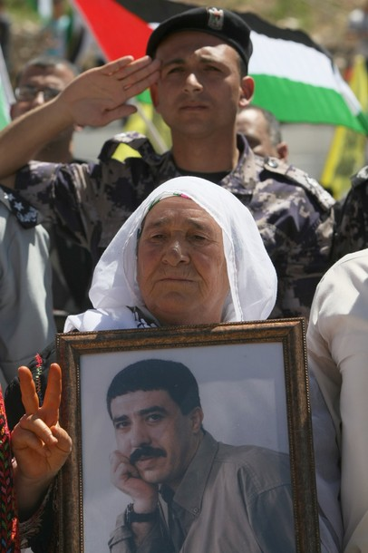 A Palestinian woman holds an image of a relative as she joins Hebron University students as they rally to mark Prisoners' Day in the West Bank town of Hebron onApril 17,2012.  At least 1,200 Palestinian inmates of Israeli jails began an open-ended hunger strike as rallies across the Israeli occupied Palestinian territories marked Prisoners' Day.  AFP PHOTO / HAZEM BADER