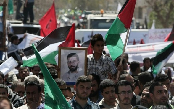 Palestinian protesters wave national flags during a rally in Gaza City on April 17, 2012 in solidarity with Palestinian prisoners held in Israel.  Some 1,200 Palestinian prisoners held in Israeli jails have begun a hunger strike and another 2,300 are refusing food for one day, a spokeswoman for the Israel Prisons Service (IPS) said as Palestinians across the West Bank and Gaza Strip were marking Prisoners' Day in solidarity with the 4,700 Palestinian inmates of Israeli jails. AFP PHOTO/MAHMUD HAMS