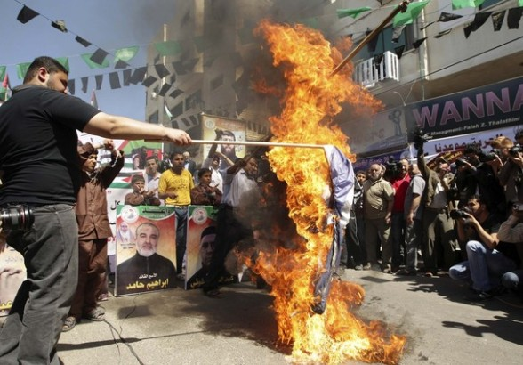 Palestinians burn Israel's national flag during a rally in front of the Red Cross headquarters in Gaza City marking Palestinian Prisoners Day April 17, 2012. The Israeli Prisons Authority said on Tuesday in a written statement that 2,300 Palestinian prisoners held in Israeli jails have said they would reject their daily meal in support of Palestinian Prisoners Day and 1,200 would launch hunger strikes.  REUTERS/Suhaib Salem