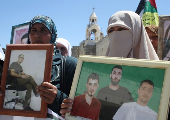 Palestinian protesters hold up pictures of incarcerated relatives during a rally  in the biblical West Bank town of Bethlehem on April 17, 2012 in solidarity with Palestinian prisoners held in Israel.  Some 1,200 Palestinian prisoners held in Israeli jails have begun a hunger strike and another 2,300 are refusing food for one day, a spokeswoman for the Israel Prisons Service (IPS) said as Palestinians across the West Bank and Gaza Strip were marking Prisoners' Day in solidarity with the 4,700 Palestinian inmates of Israeli jails. AFP PHOTO/MUSA AL-SHAER