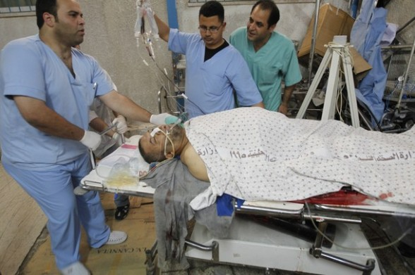 Palestinian medics receive a wounded man for treatment at a hospital  in Gaza City on May 17, 2012, following Israeli shelling into the Gaza Strip in which seven people were wounded, two of them in critical condition, near the Karni crossing.  The Israeli military maintains an exclusion zone inside the Gaza Strip along the border and regularly carries out military activity in the area.    AFP PHOTO/MOHAMMED ABED