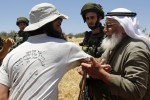 A Jewish settler (L) argues with a Palestinian farmer after Palestinian villagers were prevented by Israeli troops from working on their own lands in the West Bank village of Tuqua, east of Bethlehem, near the Jewish settlement of Tekoa on May 30, 2012. Palestinians need permission from Israeli authorities in order to be able to access their own lands located near Jewish settlements. AFP PHOTO/MUSA AL-SHAER