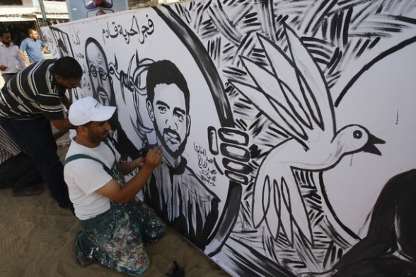 Palestinians paint a mural depicting prisoners Mahmoud Al-Sarsak (R) and Akram al-Rekhawi in Rafah, in the southern Gaza Strip June 10, 2012. Al-Sarsak and al-Rekhawi, two Palestinian prisoners held in Israeli jails, have been on hunger strike to protest against the measures of the Israeli jail administration. REUTERS/Ibraheem Abu Mustafa