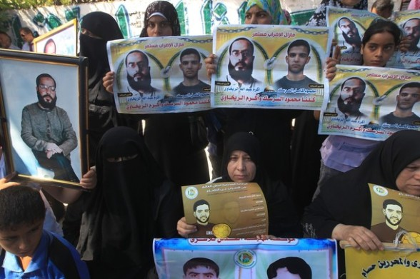 Palestinians hold posters of jailed Palestinian football player Mahmud Sarsak and prisoner Akram Rikhawi during a rally in solidarity with two Palestinian prisoners detained by Israel and still on hunger strike in Gaza City on June 11, 2012. AFP PHOTO/MAHMUD HAMS