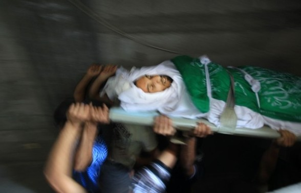 Palestinian mourners carry the body of Khaled al-Burai, 25-years-old, killed in an Israeli drone strike, during his funeral in the Jabalia refugee camp in the northern Gaza Strip on June 23, 2012. The armed wing of Hamas, which rules the Gaza Strip, threatened to end a three-day-old Egyptian-brokered truce following a flurry of Israeli air strikes. AFP PHOTO/MAHMUD HAMS