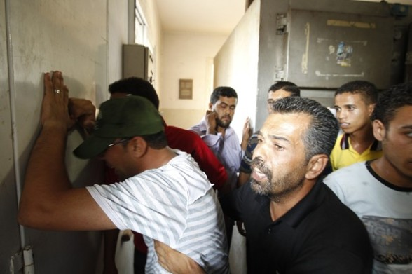 A Palestinian relative of Osama Ali grieves at the morgue after the teenager was killed in an Israeli strike on Gaza City on June 23, 2012.  The Palestinian teenager riding a motorcycle was killed, and 10 passers-by wounded in a fresh Israeli air strike on the Gaza Strip Palestinian medics said, bringing the death toll from the Israeli raids today to three.  AFP PHOTO/MOHAMMED ABED