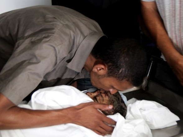 A relative kisses the body of six-year-old Palestinian, Ali al-Shawaf as he lies in the Nasser hospital morgue in Khan Yunis, in the southern Gaza Strip on June 23, 2012 after he was killed during Israeli air strikes in Gaza. Two others were wounded in the shelling, but the Israeli military denied it was responsible. AFP PHOTO/ SAID KHATIB