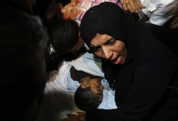 "The Palestinian mother of six-year-old boy Ali Al-Shwaf mourns next his body during his funeral in Khan Younis, in the southern Gaza Strip June 23, 2012. Hamas medical officials said a six-year-old Palestinian boy had been killed in an air strike and a that a baby had been hurt in a separate raid near the Egyptian border. Israel denied involvement in hurting either of the children. Lieutenant Colonel Avital Leibovich, an Israeli military spokeswoman, said on Twitter that the report of Israeli responsibility in the death of the six-year-old was the result of ""false rumours"" and that the boy had died due to an explosion of ordnance belonging to Palestinian militants.nother Israeli military spokeswoman said she had no report of any air strikes in Rafah, where the baby was reported to have been hurt. REUTERS/Ibraheem Abu Mustafa"