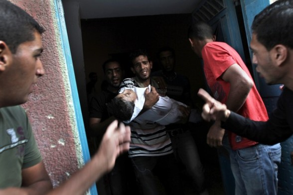 A Palestinian man carries the body of six-year-old Ali al-Shwaf out of his house for his funeral in Khan Younis, in the southern Gaza Strip on June 23, 2012, after he was killed during an Israeli air strike in Gaza as his father and another man were wounded in the shelling, but the Israeli military denied it was responsible. AFP PHOTO/SAID KHATIB