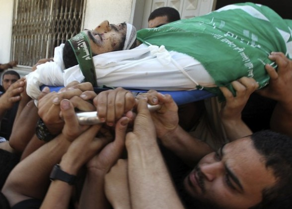 Palestinians carry the body of Hamas militant Hamam Abu Qadus during his funeral in Gaza City June 23, 2012. Israel launched air raids early on Saturday against three Hamas security targets in the Gaza Strip, wounding at least 17 people, Hamas medical officials said. The Israeli military confirmed its aircraft had struck two militant targets in Gaza overnight, calling it a response to rocket fire aimed at Israel from the Islamist-ruled territory. REUTERS/Mohammed Salem