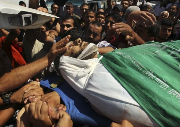 Palestinians carry the body of Hamas militant Hamam Abu Qadus during his funeral in Gaza City June 23, 2012. Israel launched air raids early on Saturday against three Hamas security targets in the Gaza Strip, wounding at least 17 people, Hamas medical officials said.The Israeli military confirmed its aircraft had struck two militant targets in Gaza overnight, calling it a response to rocket fire aimed at Israel from the Islamist-ruled territory. REUTERS/Mohammed Salem