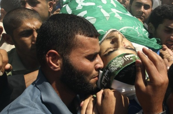 A Palestinian mourns next to the body of Hamas militant Hamam Abu Qadus during his funeral in Gaza City June 23, 2012. Israel launched air raids early on Saturday against three Hamas security targets in the Gaza Strip, wounding at least 17 people, Hamas medical officials said.The Israeli military confirmed its aircraft had struck two militant targets in Gaza overnight, calling it a response to rocket fire aimed at Israel from the Islamist-ruled territory. REUTERS/Mohammed Salem