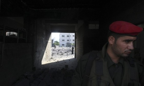 A member of Hamas' security forces stands guard next a damaged Hamas security site in Gaza City June 23, 2012. Israel launched air raids early on Saturday against three Hamas security targets in the Gaza Strip, wounding at least 17 people, Hamas medical officials said. REUTERS/Mohammed Salem
