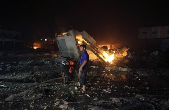 Palestinians try to douse a fire after Israeli aircrafts hit a Hamas security site in Gaza City June 23, 2012.  Israel launched air raids early on Saturday against three Hamas security targets in the Gaza Strip, wounding at least 17 people,  Hamas medical officials said.   REUTERS/Mohammed Salem