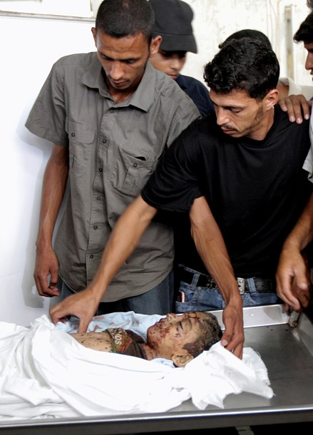 Palestinians look at the body of six-year-old Palestinian, Ali al-Shawaf at the Nasser hospital morgue in Khan Yunis, in the southern Gaza Strip on June 23, 2012 after he was killed during Israeli air strikes in Gaza. Two others were wounded in the shelling, but the Israeli military denied it was responsible. AFP PHOTO/ SAID KHATIB