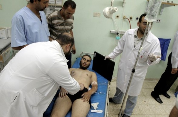 A Palestinian medic tends to a man who was wounded during Israeli air strikes on the southern Gaza Strip, at the European Union (EU) hospital in Khan Yunis on June 23, 2012. A six-year-old boy was killed and two other Palestinians wounded in Gaza on June 23, but the Israeli military denied it was responsible. AFP PHOTO/ SAID KHATIB