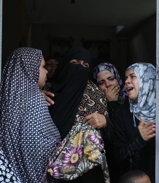 Female Palestinian relatives grieve during the funeral of Osama Ali after he was killed in an Israeli strike on Gaza City on June 23, 2012. Three Palestinians were killed and an Israeli wounded in air raids and rocket fire, medics said, as the armed wing of Hamas threatened to call off an Egypt-brokered truce. AFP PHOTO/MOHAMMED ABED