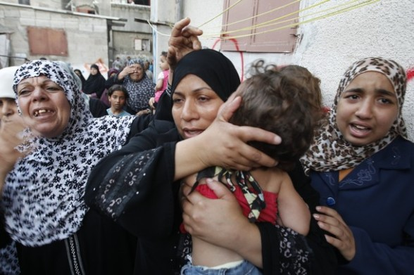 A Palestinian female relative holds a child during the funeral of Osama Ali, killed in an Israeli strike on Gaza City on June 23, 2012. The Palestinian teenager riding a motorcycle was killed, and 10 passers-by wounded in a fresh Israeli air strike on the Gaza Strip Palestinian medics said, bringing the death toll from the current Israeli raids to three. AFP PHOTO/MOHAMMED ABED