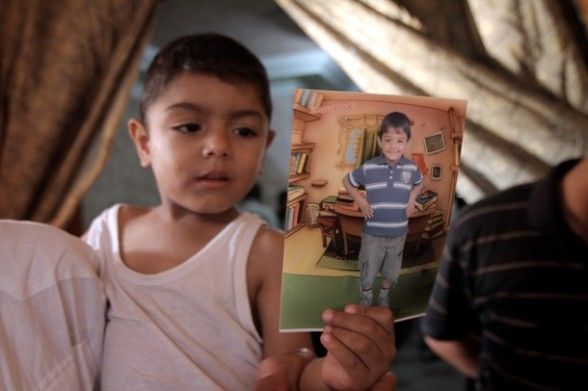 Palestinian Abed Al hai holds a picture of his six-year-old brother, Ali al-Shwaf during his funeral in Khan Younis, in the southern Gaza Strip on June 23, 2012, after he was killed during an Israeli air strike in Gaza and his father and another man were wounded in the shelling, but the Israeli military denied it was responsible. AFP PHOTO/SAID KHATIB