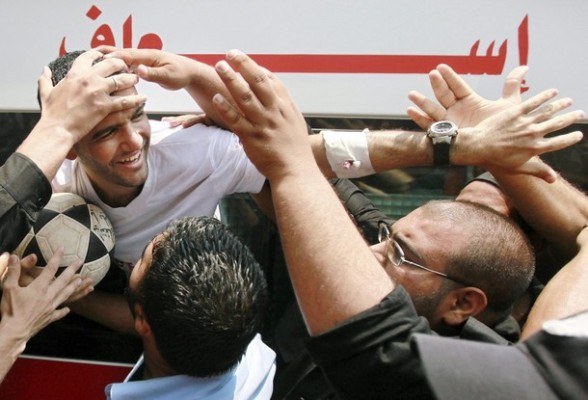 Palestinian soccer player Mahmoud Al-Sarsak (L) is greeted upon his arrival in Gaza City July 10, 2012. Israel released the Gaza soccer player on Tuesday in a deal to end his intermittent four-month hunger strike after he spent three years behind bars without being put on trial, officials said. REUTERS/Mohammed Salem