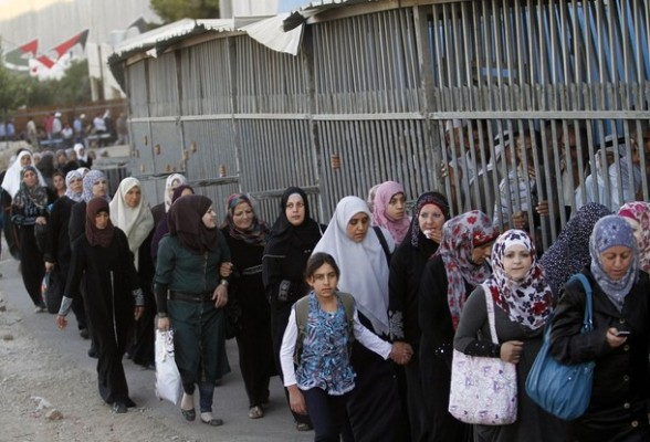 Palestinian women pass through an Israeli checkpoint in the open air while men are required to pass through a barred passageway on their way to pray at the Al-Aqsa Mosque in Jerusalem, on the fourth Friday of the Muslim holy month of Ramadan near Bethlehem, West Bank, Friday, Aug. 10, 2012. Ramadan is the ninth month of the Muslim year which lasts 30 days, and is devoted to dawn-to-dusk fasting, prayers and good deeds.  (AP Photo/Nasser Shiyoukhi)