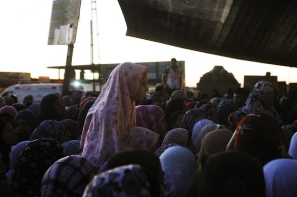 A Palestinian girl sits on the shoulders of a woman as they wait to cross at Israel's Qalandiya checkpoint outside the West Bank city of Ramallah on the fourth Friday of the holy month of Ramadan August 10, 2012. REUTERS/Mohamad Torokman