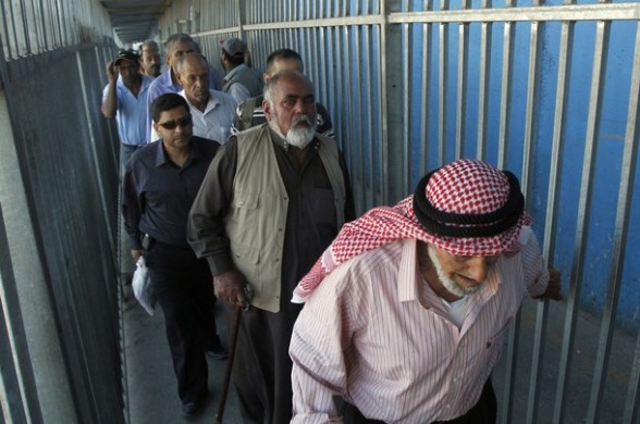 Palestinian Muslim men cross a checkpoint along Israel's controversial separation barrier on the outskirts of the West Bank town of Bethlehem on their way to Jerusalem to attend the Friday prayers at the Al-Aqsa mosque on August 10, 2012. Muslims across the world have been fasting during the holy month of Ramadan which is expected to end around August 19th. AFP PHOTO/MUSA AL SHAER