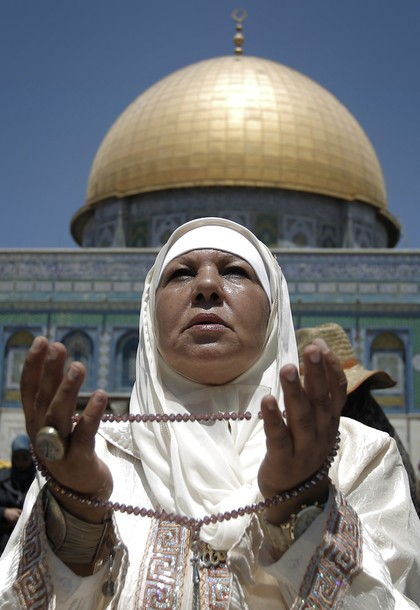 A Muslim woman prays outside the Dome of the Rock mosque situated in the al-Aqsa mosque compound, Islam?s third most holy site, on August 10, 2011 in old city of Jerusalem, on the Friday of the Islamic holy month of Ramadan. AFP PHOTO /AHMAD GHARABLI