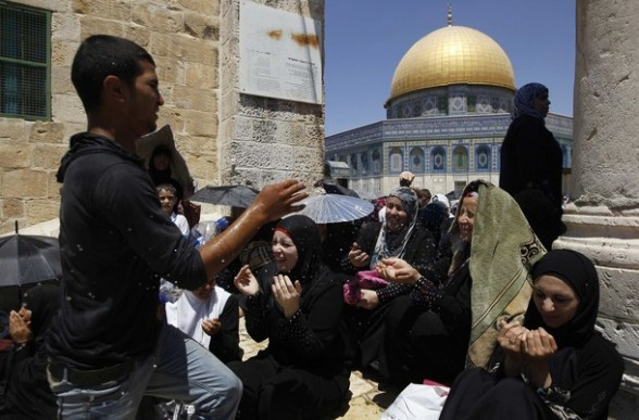A Palestinian boy splashes women with water to cool them down near the Dome of the Rock (rear) on the compound known to Muslims as Noble Sanctuary and to Jews as Temple Mount in Jerusalem's Old City, on the fourth Friday of the holy month of Ramadan August 10, 2012. REUTERS/Ammar Awad