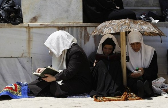Palestinian women read the Koran on the compound known to Muslims as Noble Sanctuary and to Jews as Temple Mount in Jerusalem's Old City, on the fourth Friday of the holy month of Ramadan August 10, 2012. REUTERS/Ammar Awad