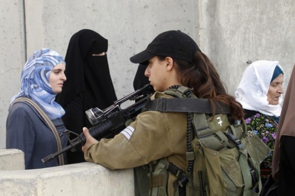 An Israeli border policewoman stands guard as Palestinian Muslim women queue to cross a checkpoint along Israel's controversial separation barrier on the outskirts of the West Bank town of Bethlehem on their way to Jerusalem to attend the Friday prayers at the Al-Aqsa mosque on August 10, 2012. Muslims across the world have been fasting during the holy month of Ramadan which is expected to end around August 19th. AFP PHOTO/MUSA AL SHAER