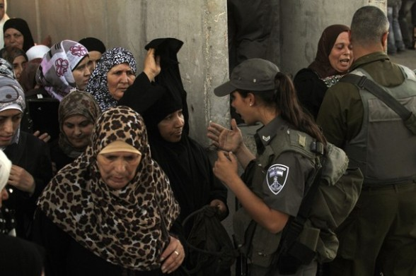 Palestinian Muslim women queue to cross an Israeli checkpoint along Israel's controversial separation barrier on the outskirts of the West Bank town of Bethlehem on their way to Jerusalem to attend the Friday prayers at the Al-Aqsa mosque on August 10, 2012. Muslims across the world have been fasting during the holy month of Ramadan which is expected to end around August 19th. AFP PHOTO/MUSA AL SHAER