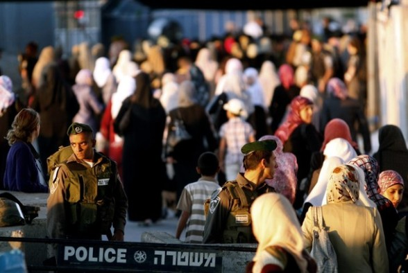 Israeli soldiers stand guard as Palestinian women pass an Israeli checkpoint on their way to pray at the Al-Aqsa Mosque in Jerusalem, on the fourth Friday of the Muslim holy month of Ramadan near the West Bank city of Ramallah, Friday, Aug. 10, 2012.  Ramadan is the ninth month of the Muslim year which lasts 30 days, and is devoted to dawn-to-dusk fasting, prayers and good deeds. (AP Photo/Majdi Mohammed)