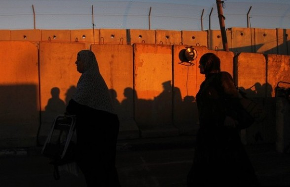 Palestinian women walk past a section of Israel's controversial barrier at Qalandiya checkpoint outside the West Bank city of Ramallah, on the fourth Friday of the holy month of Ramadan, August 10, 2012. REUTERS/Mohamad Torokman