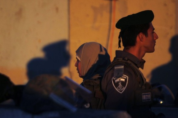 A Palestinian woman stands behind an Israeli border policeman as Palestinians cross at Qalandiya checkpoint outside the West Bank city of Ramallah on the fourth Friday of the holy month of Ramadan August 10, 2012. REUTERS/Mohamad Torokman