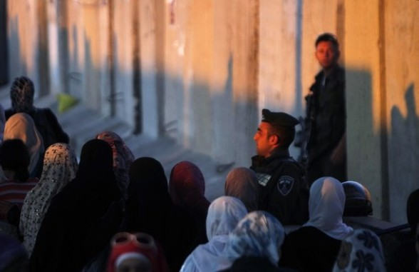 Palestinian women walk past Israeli security officers as they cross at Qalandiya checkpoint outside the West Bank city of Ramallah on the fourth Friday of the holy month of Ramadan August 10, 2012. REUTERS/Mohamad Torokman