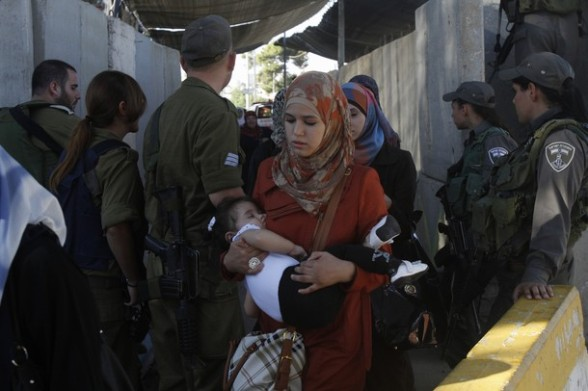 Israeli security forces monitor the crossing of Palestinian Muslim women at checkpoint along Israel's controversial separation barrier on the outskirts of the West Bank town of Bethlehem on their way to Jerusalem to attend the Friday prayers at the Al-Aqsa mosque on August 10, 2012. Muslims across the world have been fasting during the holy month of Ramadan which is expected to end around August 19th. AFP PHOTO/MUSA AL SHAER