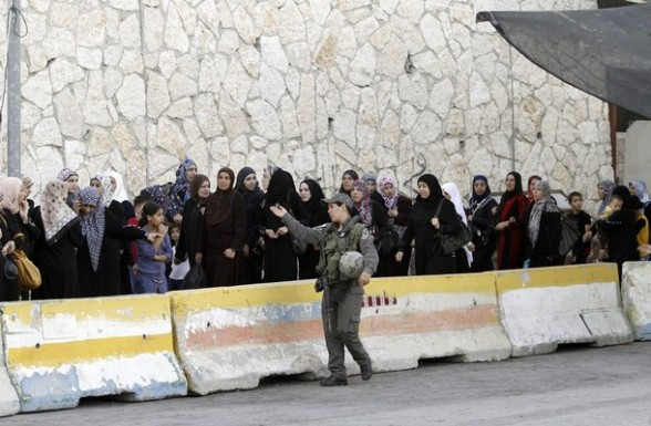 An Israeli soldier oversees Palestinian women and children passing through an Israeli checkpoint on their way to pray at the Al-Aqsa Mosque in Jerusalem on the fourth Friday of the Muslim holy month of Ramadan near Bethlehem, West Bank, Friday, Aug. 10, 2012. Ramadan is the ninth month of the Muslim year which lasts 30 days, and is devoted to dawn-to-dusk fasting, prayers and good deeds. (AP Photo/Nasser Shiyoukhi)